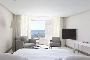 Chambre vaste ouverte sur une terrasse avec vue sur la mer.