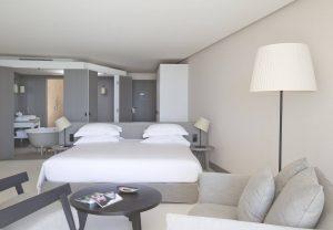 Chambre meublée d'un lit king size, d'une télévision et de fauteuils confortables